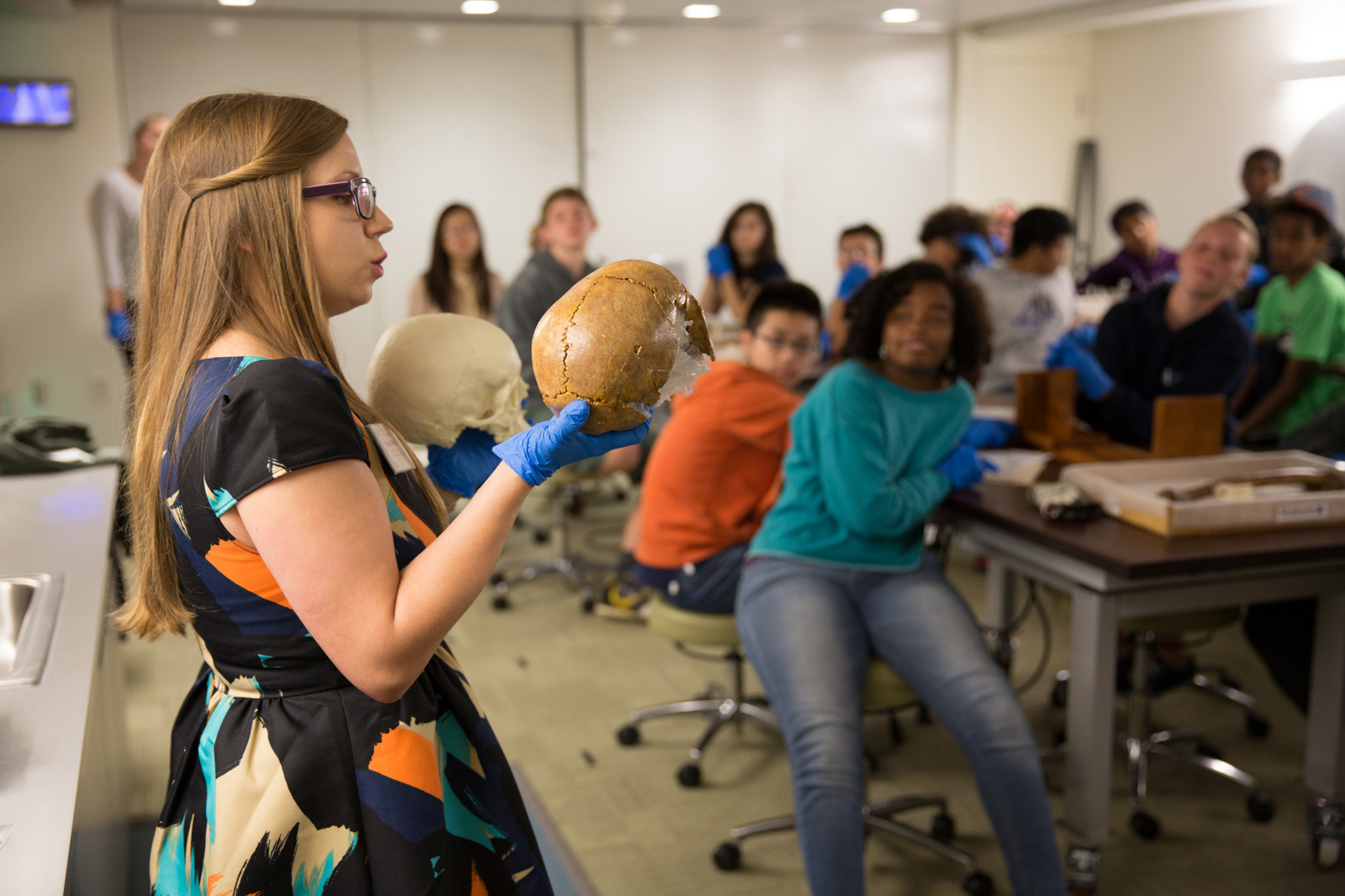 A museum educator holds up two models of human skulls during a school program in Q?rius.
