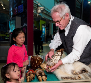 Archaeologist Stephen Loring in museum exhibit, showing children samples of fur