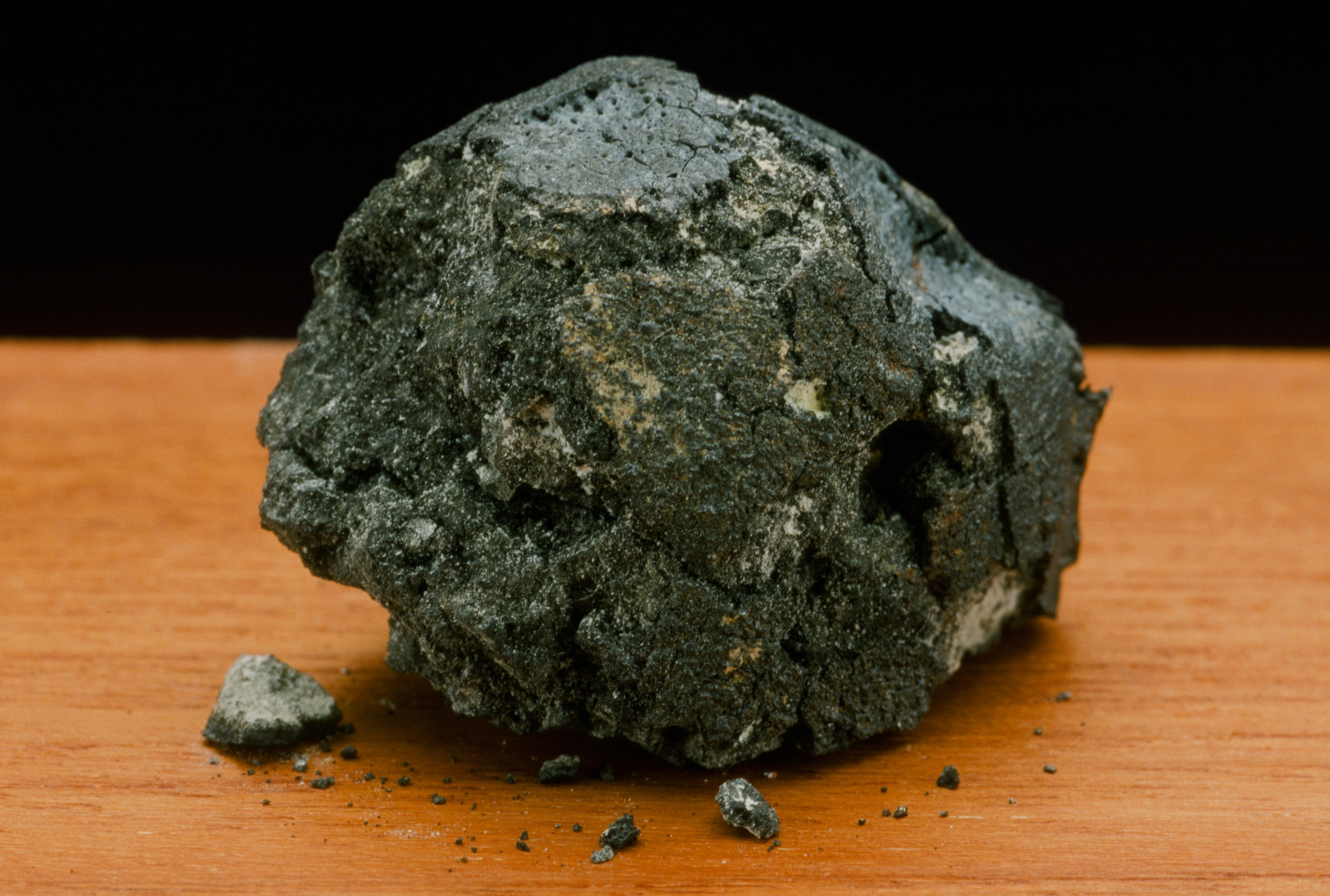 A carbonaceous chondrite on a wooden surface