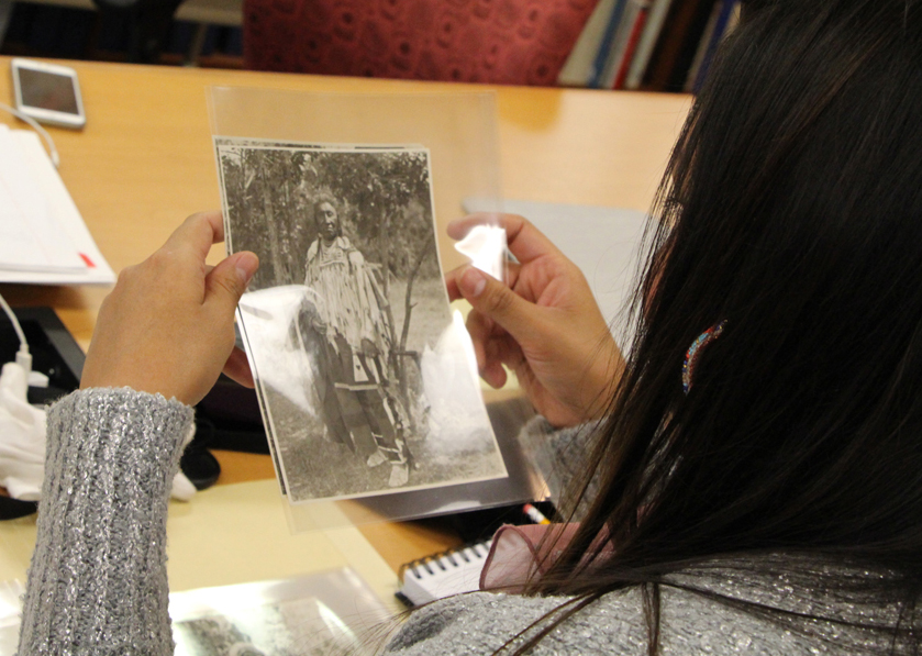 Woman looking at old, archival photograph of a man in traditional Apsaalooke (Crow) clothing