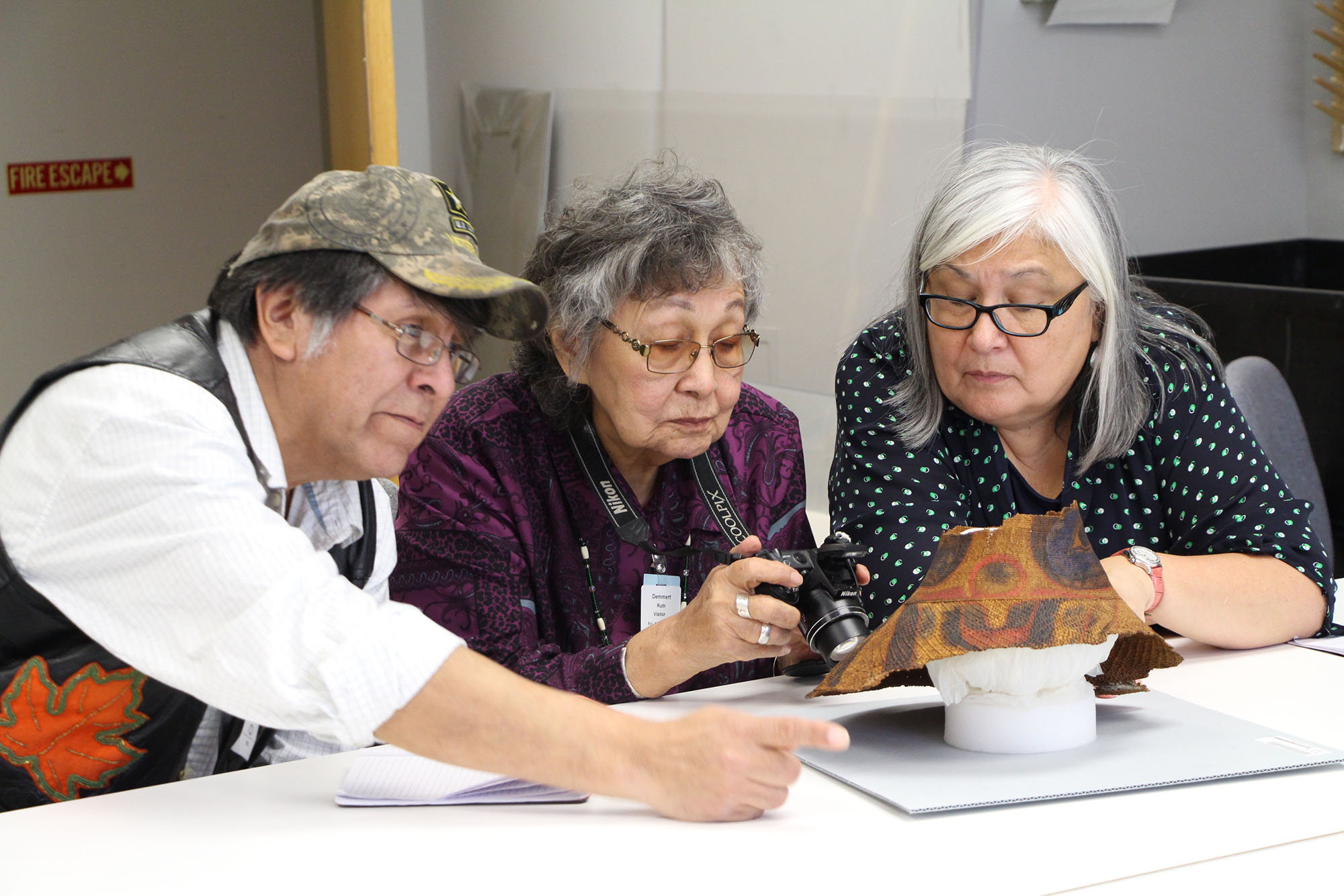 Three Tlingit tribal elders examine traditional hat in collections